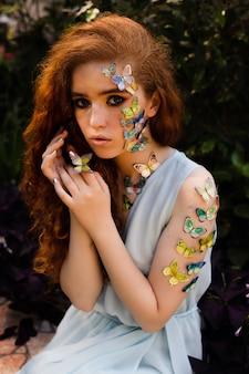Молодая рыжая девушка с бабочками на лице