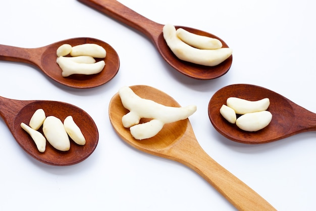 Young ginger peeled in wooden spoons on white background.