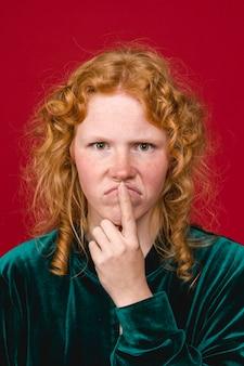 Молодая рыжая задумчивая женщина морщится и трогает губы