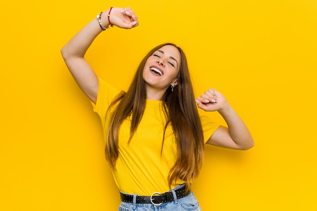 Young ginger redhead woman celebrating a special day, jumps and raise arms with energy.
