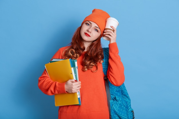 Young ginger student in casual clothes, has backpack, holds disposable cup near face, stands with paper folder