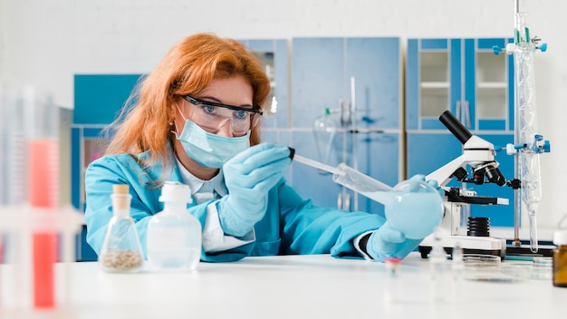 Young ginger woman chemist working in her lab