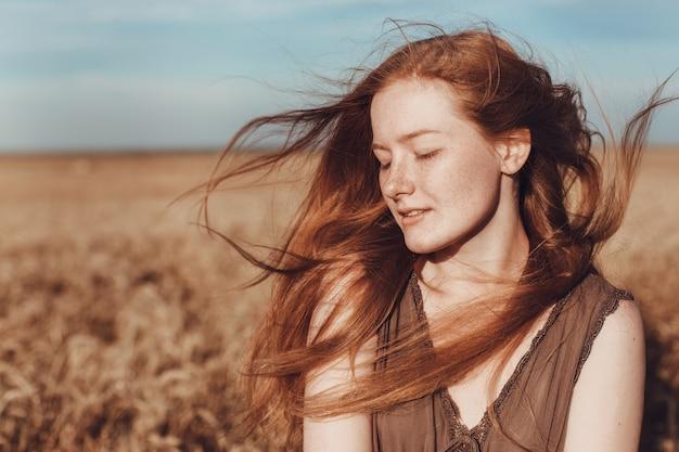 Молодая женщина имбиря в пшеничном поле выглядит расслабленным. женщина в сельскохозяйственном поле во время заката.