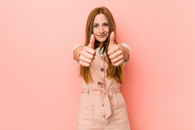 Young ginger woman with freckles with thumbs ups, cheers about something, support and respect concept.