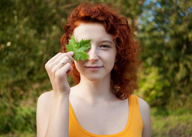 그녀의 손에 녹색 잎을 가진 젊은 생강 여자