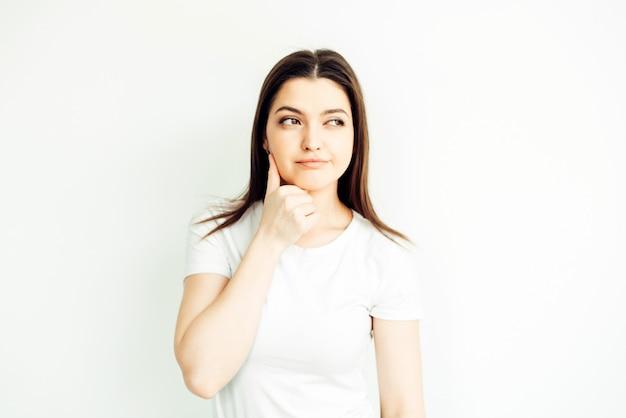 25歳の少女、感情-疑い。白色の背景