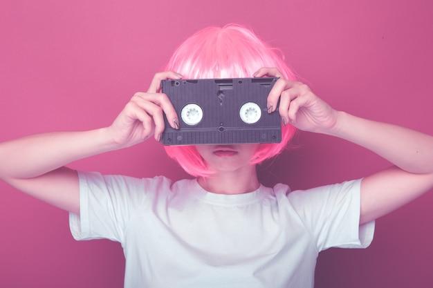 Молодая девушка 90-х и кассета vhs на розовом фоне.