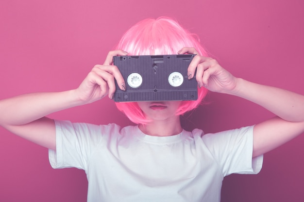 Young girl 90s and vhs cassette on pink background.