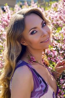 若い女の子晴れた日にアーモンドの木amygdalusのピンクの小さな花