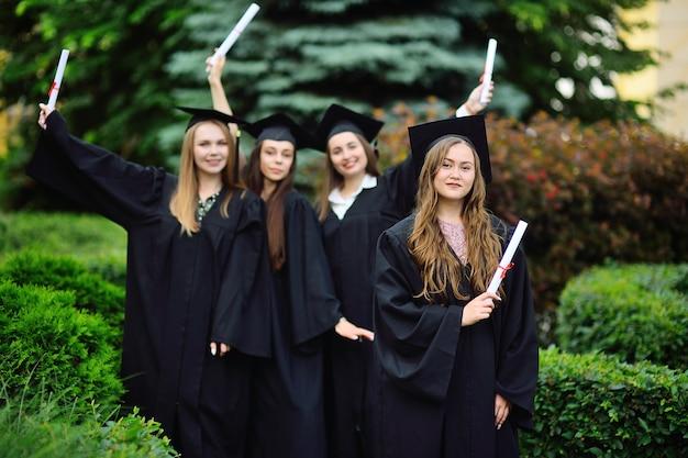 黒いローブを着た大学の大学院生で、卒業証書を手にした四角い帽子をかぶった少女は、学生のクラスメートを背景に微笑んでいます。