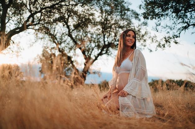 속옷 차림으로 사진을 찍고 있는 자연 속에서 아기를 낳으려는 어린 소녀