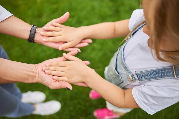 녹색 잔디에 서있는 동안 어린 소녀와 성인 여성이 함께 손을 잡고