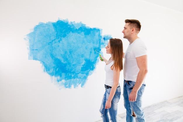 Молодая девушка и мальчик красят стену
