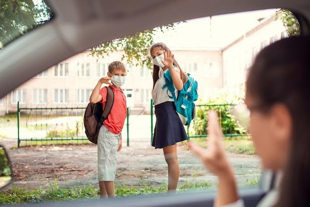 Молодая девушка и ее брат в медицинских масках с рюкзаками машут на прощание своим родителям