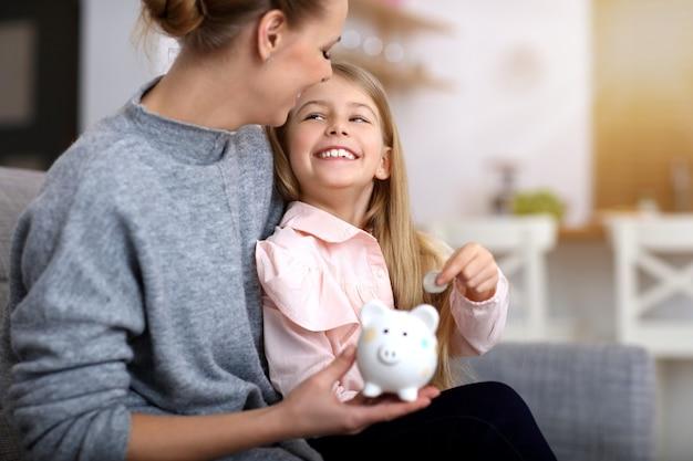 어린 소녀와 그녀의 어머니 piggybank 테이블에 앉아