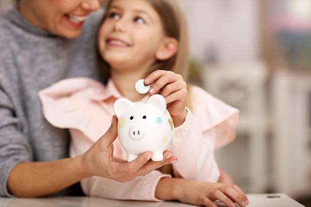 若い女の子とテーブルに座っている piggybank を持つ彼女の母親