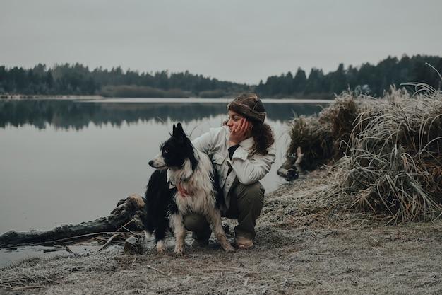 冬を楽しんでいる少女と彼の犬