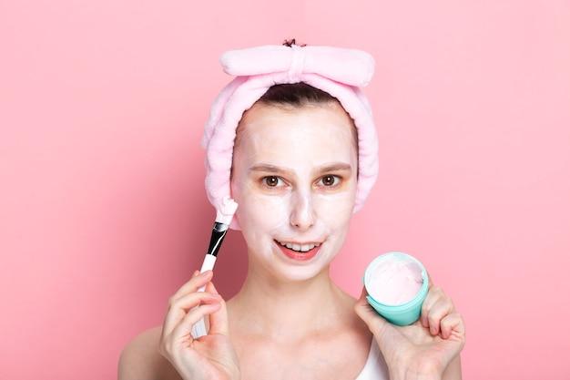 Молодая девушка применяет косметическую маску с кистью и улыбками. концепция спа-дня дома, отдыха и релаксации