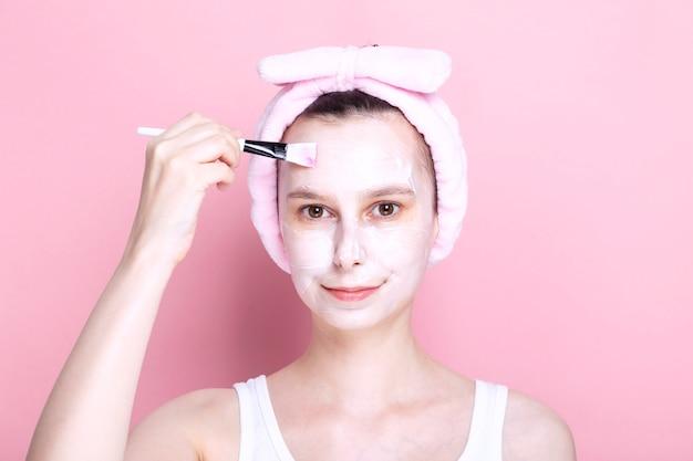 Молодая девушка наносит косметическую маску кистью. концепция спа-дня дома, отдыха и релаксации