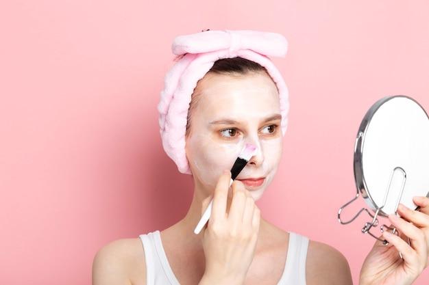 Молодая девушка применяет косметическую маску с кистью, смотрит в зеркало. концепция спа-дня дома, отдыха и релаксации