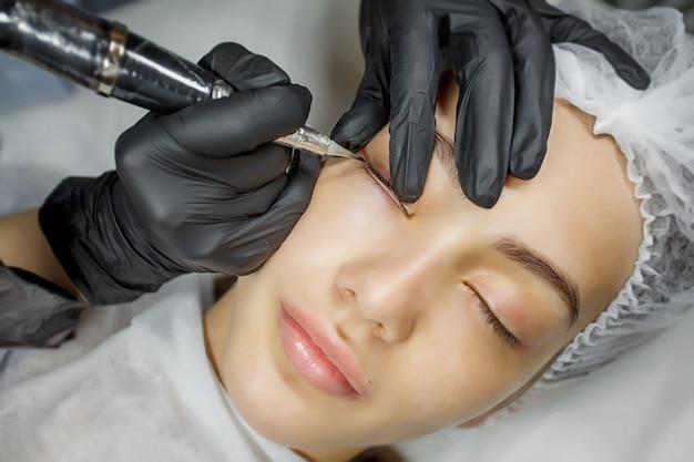 Young girl applying permanent eyeliner in beauty studio