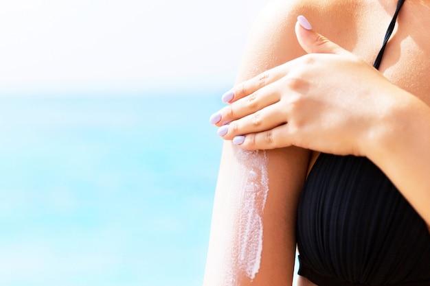 Young girl applying sunscreen on her showlder
