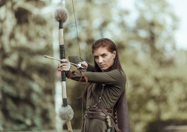 Стрельба из лука молодой девушки в цель, атмосферная фотография с размытым фоном