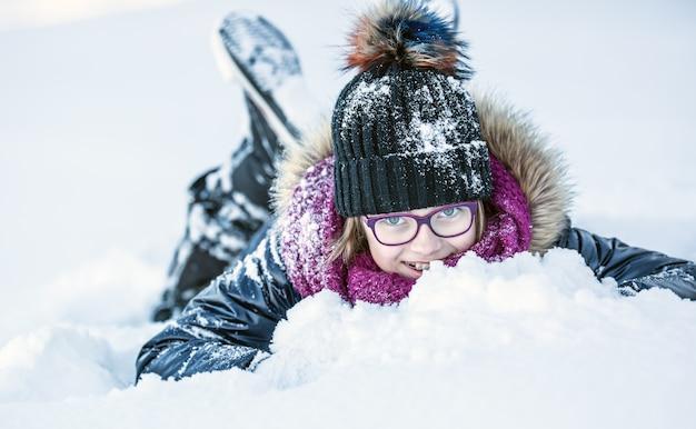 若い女の子が雪で遊んでいる凍るような冬の公園で幸せな女の子にクローズアップ