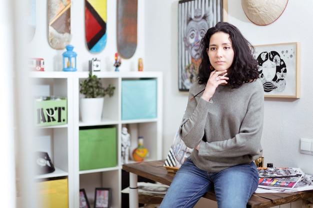 彼女のアートスタジオの若い女の子のアーティストは、彼女の作品の1つをしんみりと考えています。