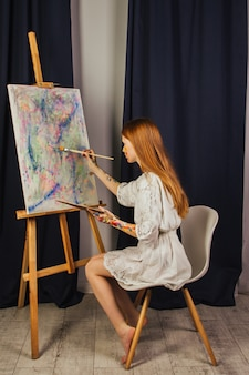 The young girl of the artist in a light white dress, paints a picture on canvas in the workshop. the face is stained with paints. a young student uses brushes, canvases and easels. creative work.