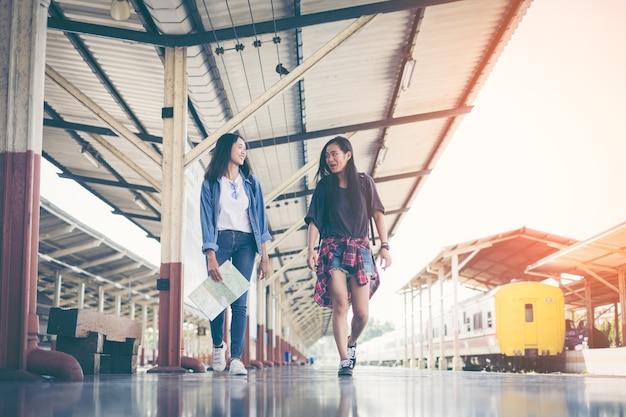 Молодая девушка азиатских рюкзак путешественник вместе ожидания с удержанием карты на вокзале