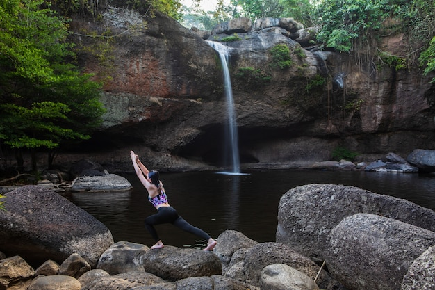 Young girl asian women is playing yoga in front of the waterfall