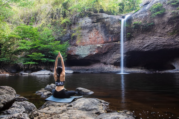 Young girl asian women is playing  yoga in front of the waterfall.