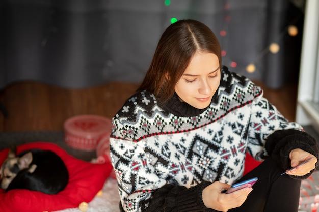 집에 작은 강아지를 안고 있는 어린 소녀가 신용 카드로 전화로 크리스마스 선물을 온라인으로 선택합니다
