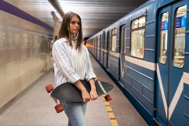Молодая девушка на платформе метро смотрит на вагон метро на станции метро в одиночку, держа лонгборд