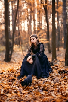 Young girl in the autumn forest is sitting on a stump. a black cat walks nearby.