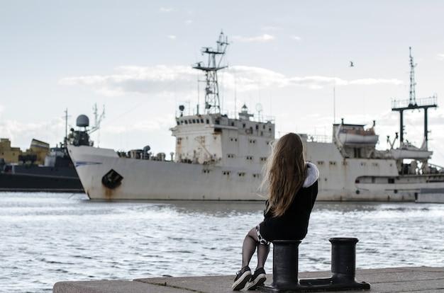 배를 보고 어린 소녀 다시 보기입니다. 바다 여행을 꿈꾸는 여성