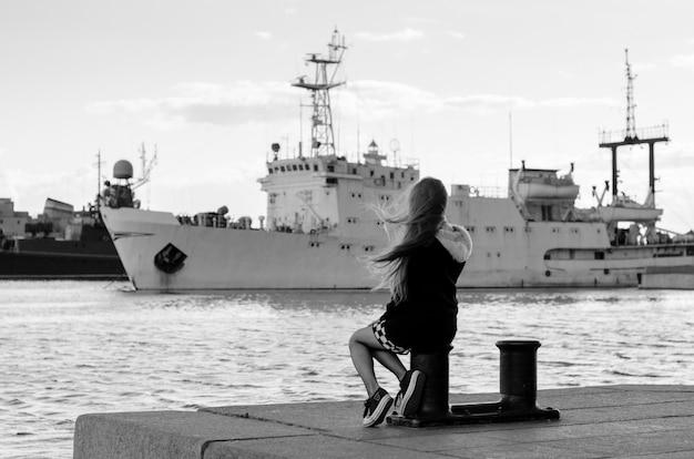 배를 보고 어린 소녀 다시 보기입니다. 바다 여행을 꿈꾸는 여자.