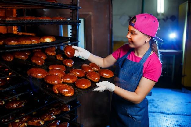 Пекарь молодой девушки держит поднос с горячей выпечкой на фоне промышленной печи в пекарне. производство хлебобулочных изделий. решетка для свежего хрустящего теста Premium Фотографии