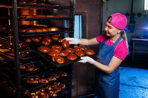Пекарь молодой девушки держит поднос с горячей выпечкой на фоне промышленной печи в пекарне. производство хлебобулочных изделий. решетка для свежего хрустящего теста