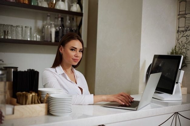 A young girl behind the bar works on a laptop and smiles