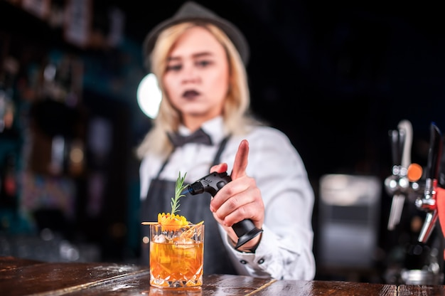 Молодая девушка-бармен демонстрирует процесс приготовления коктейля в ночном клубе