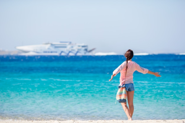 Young girl on the beach background big cruise liner. woman enjoy her wekeend on one of the beautiful beaches in greece, europe.