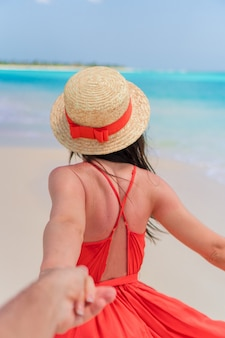 Young girl in beautiful red dress in the beach