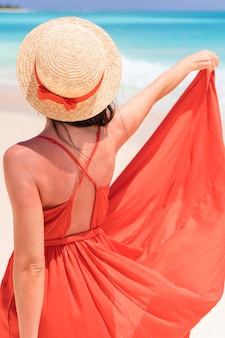 Young girl in beautiful red dress in the seashore