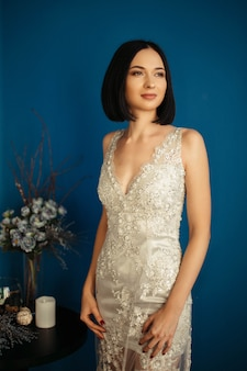 Young girl in a beautiful silvery embroidered evening dress. modern fashion style trends. new look for holiday event.