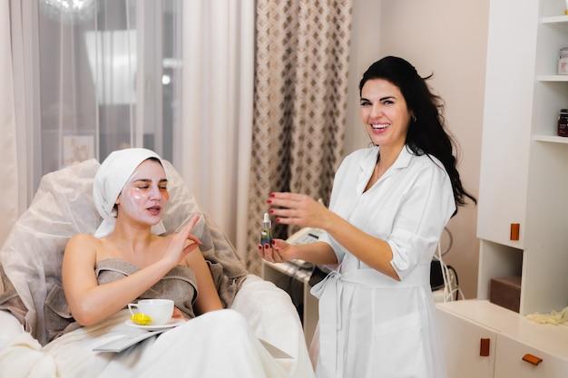 Una giovane ragazza in un salone di bellezza in un ufficio di cosmetologia giace sul letto si rilassa con una maschera sul viso