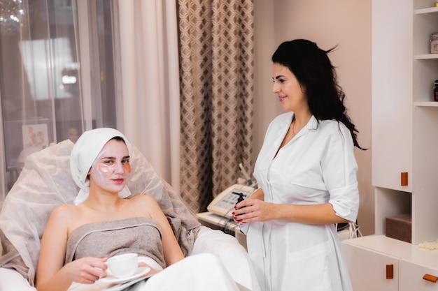 Una giovane ragazza in un salone di bellezza in un ufficio di cosmetologia si trova sul letto si rilassa con una maschera