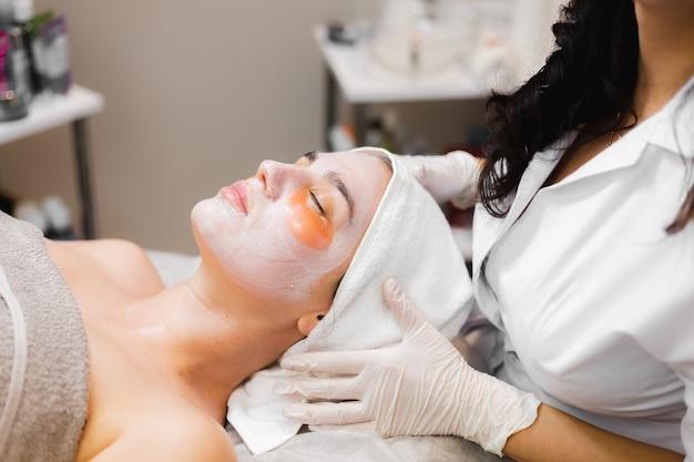 Una giovane ragazza in un salone di bellezza in una stanza di cosmetologia giace su un letto si rilassa con una maschera sul viso e le toppe sotto gli occhi