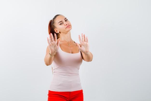 Giovane ragazza in top beige e pantaloni rossi che mostra il gesto di restrizione e che sembra serio, vista frontale.